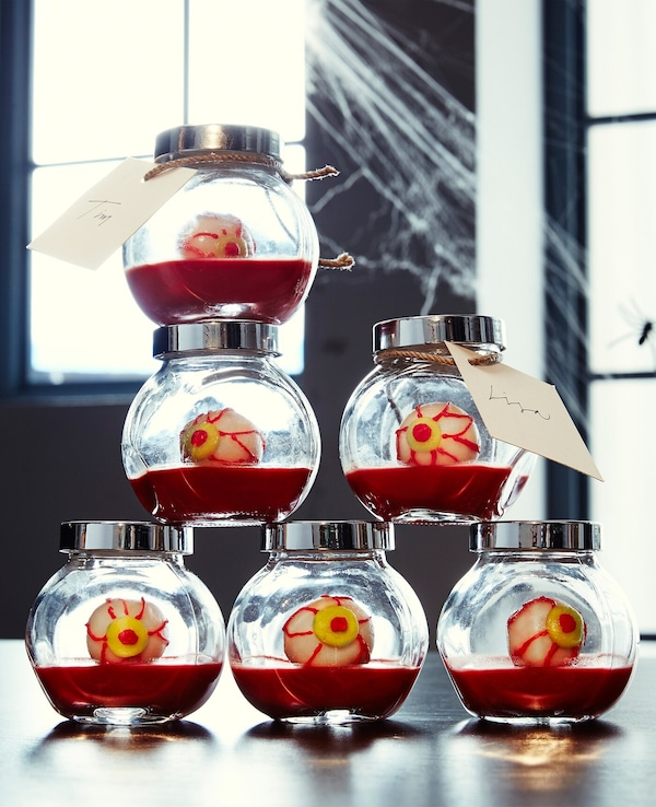 Six glass spice jars filled with faux blood and eyeballs sit on a table stacked with cobwebs around them