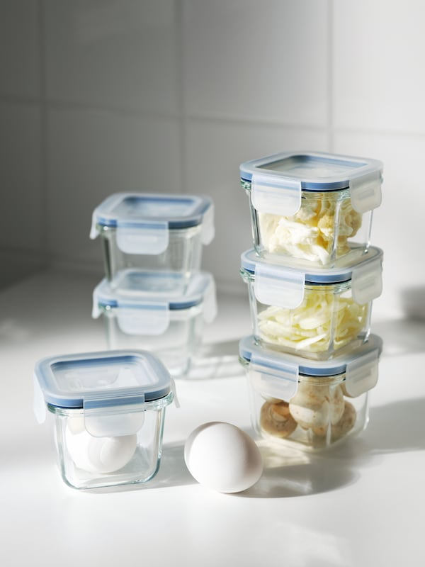Six IKEA 365+ square glass food containers with lid arranged in three stacks, holding various types of food including eggs.