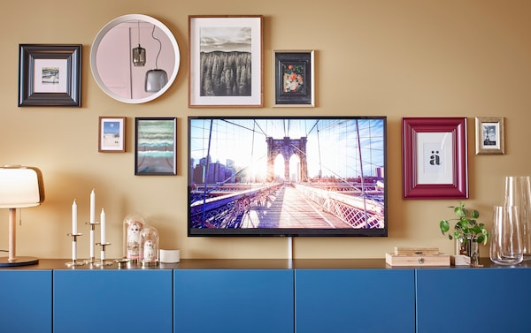 Six IKEA BESTÅ blue cabinets, with a gallery wall collage of picture frames and a mirror above it.