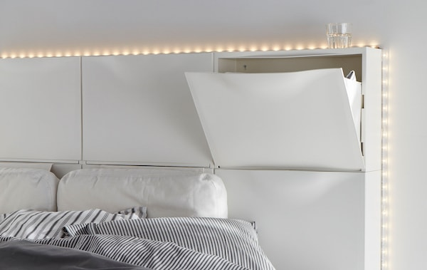 Six white IKEA TRONES shoe cabinets are wall-mounted to create a headboard for a bed in this white bedroom.