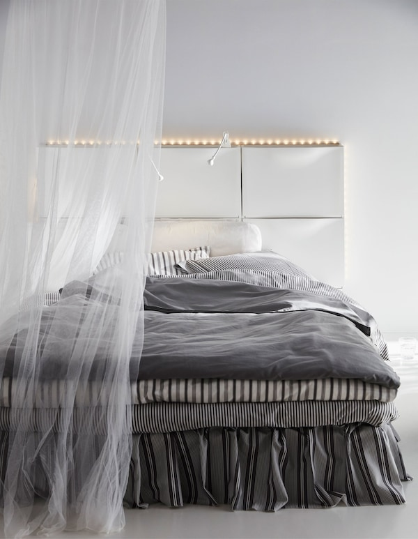 Six white IKEA TRONES shoe cabinets create a headboard for a bed in this white bedroom.