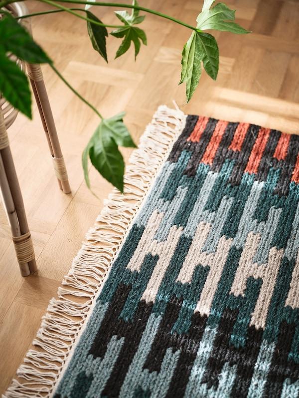 سجادRESENSTAD ألوان متعددة بجوار طاولة خيزران مع نبات أخضر على السطح في غرفة فاتحة.