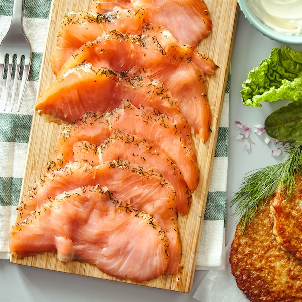 SJÖRAPPORT cured cold smoked salmon on a wooden chopping board placed on a striped tea towel with a metal fork beside.