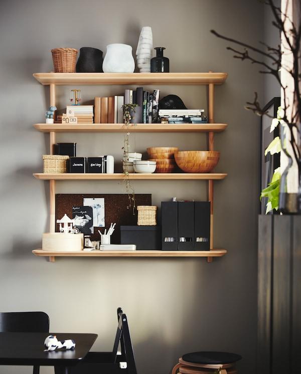 Skålar, tidskriftssamlare, porslin och böcker förvaras på fyra vägghyllor i askfaner, som satts upp på väggen bredvid ett bord.