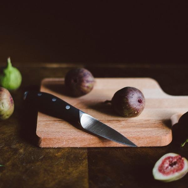 Skalkniv och fikon på en skärbräda.