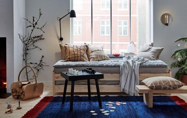 Skąpo umeblowany pokój dzienny z łóżkiem ułożonym jeden na drugim pod oknem, poduszkami, tekstyliami, dwoma stolikami kawowymi, dużym dywanem.