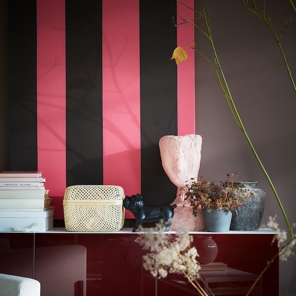 Škatuľa SMARRA s bambusovým vrchnákom položená na bielo-červenej skrinke spolu s ďalšími dekoráciami.