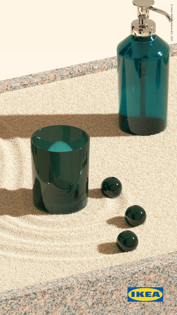 SKISSEN tvålpump och tandborsthållare i grönt glas står på gula sandvirvlar framför en gul bakgrund.