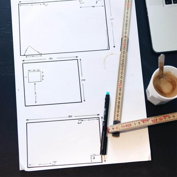 Skizzen eines Raumes auf weißem Papier mit Rollmeter