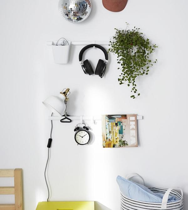 سكك التعليق الموفرة للمساحة تساعدك في تنظيم أغراضك والتخلص من الفوضى من خلال حمل أغراض مثل ساعة منبه، وأواني نباتات، ومصباح قراءة ومجلات.