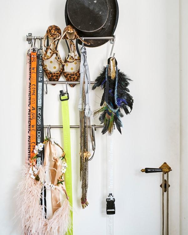 سكك تعليق معدنية للمطبخ على باب أبيض وعليها إكسسوارات بما في ذلك قبعة، وأحذية بطباعة فهد وقلائد وأشرطة.