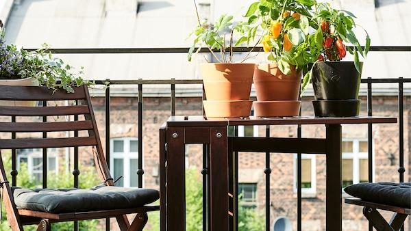 Skladací stôl a stoličky na balkóne sa sadenicami.