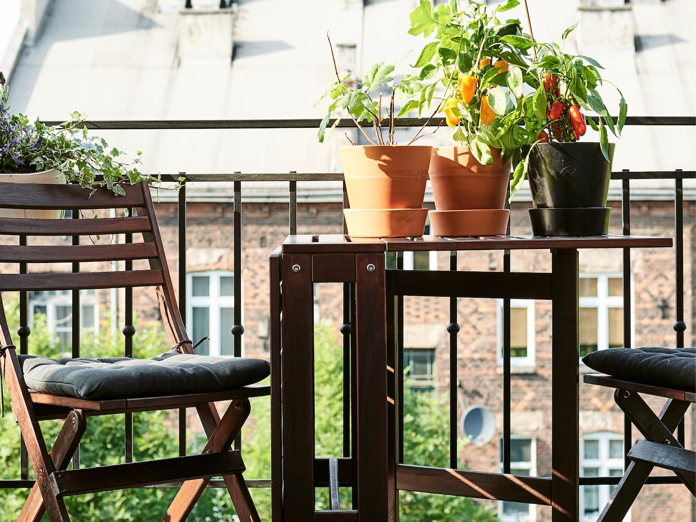 Skládací stůl a židle na balkoně se sazenicemi.