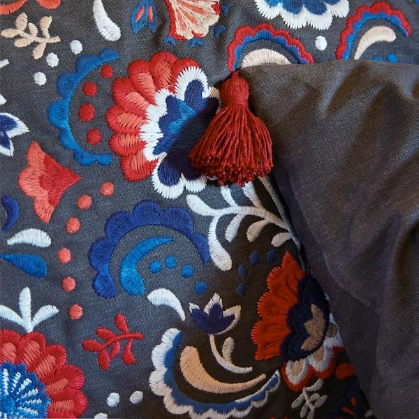 SKOGSKORN-koristetyynyn kukkakirjonta lisää tyynyyn rakennetta ja kiiltoa, ja kulmien tupsut täydentävät perinteisen tyylin.