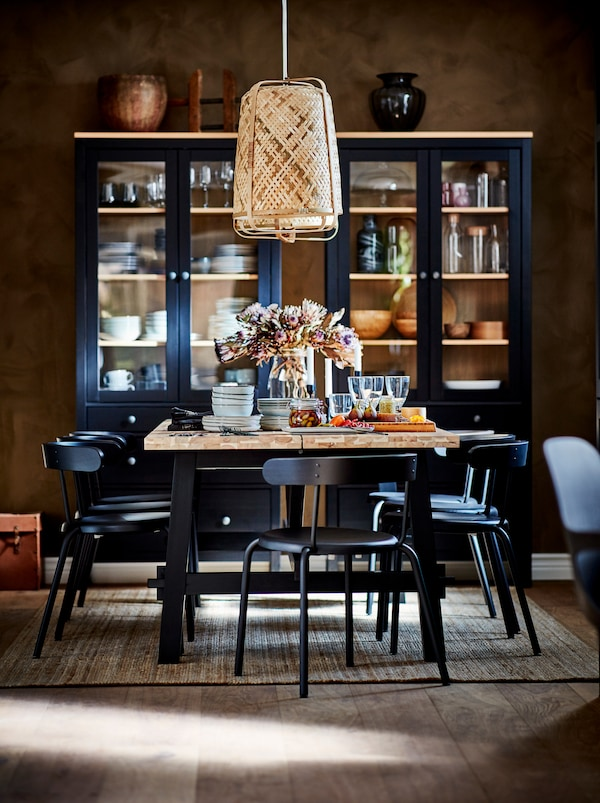 SKOGSTA blagovaonski stol postavljen je ispod visilice. Tamne vitrine s dodacima za stol nalaze se pokraj udaljenog zida.