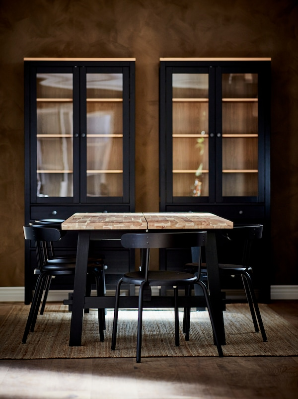 SKOGSTA dining table, with light-wood top and dark legs, surrounded by anthracite YNGVAR chairs. Dark cabinets by the wall.