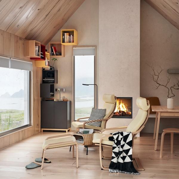 Skrinka EKET v antracitovej farbe s dvierkami so zabudovaným tlakovým otváraním v obývacej izbe s kreslami a dvomi oknami.