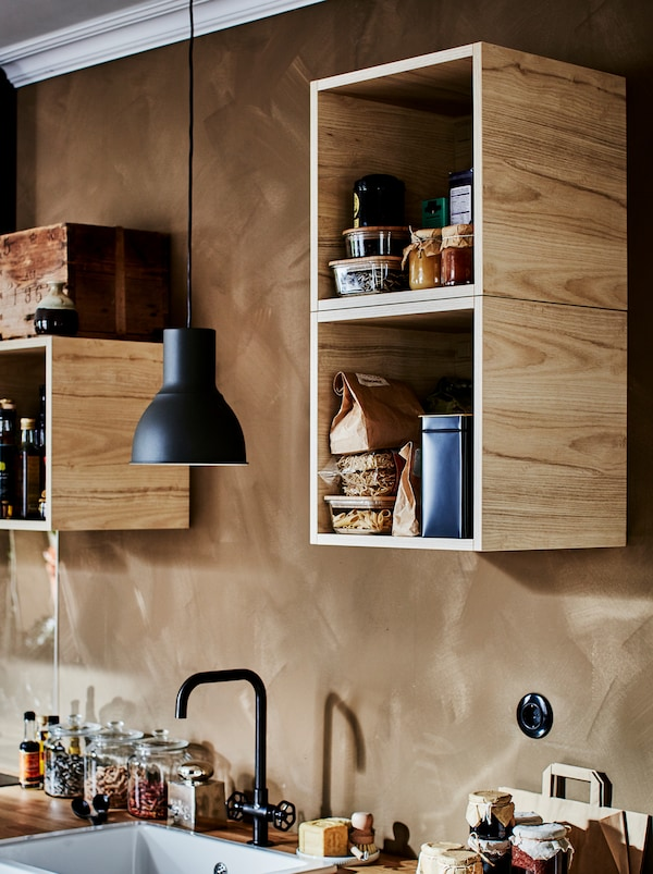 Skrinky TUTEMO s rozličnými kuchynskými doplnkami nerovnomerne rozmiestnené na stene v kuchyni.