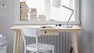 Skrivbord i ljust trä och vit stol stående framför ett fönster.