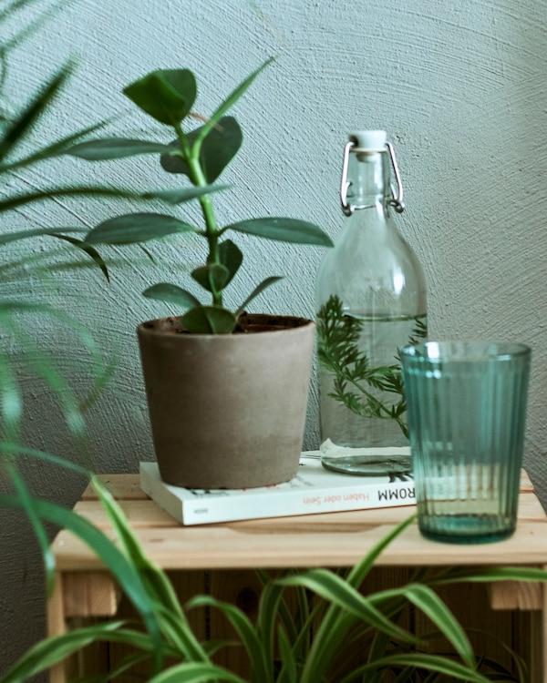 Skrzynka służąca za stolik nocny z rośliną w brązowej doniczce, szklaną butelką z wodą z ziołami w szklanej butelce i zielonym, szklanym kubkiem.