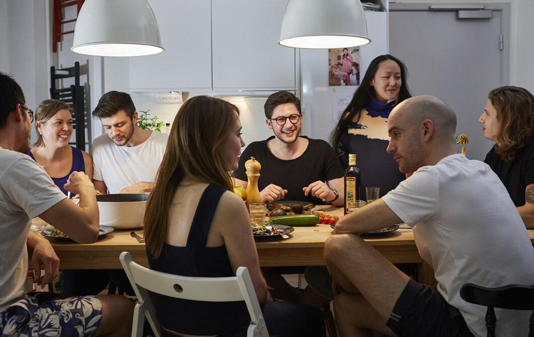 Skupina ľudí večeria a diskutuje pri stole v komunitnej kuchyni v spoločnom bývaní Nest v Kodani.