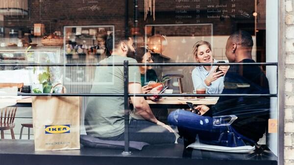 Skupina přátel sedící v kavárně s taškou IKEA.
