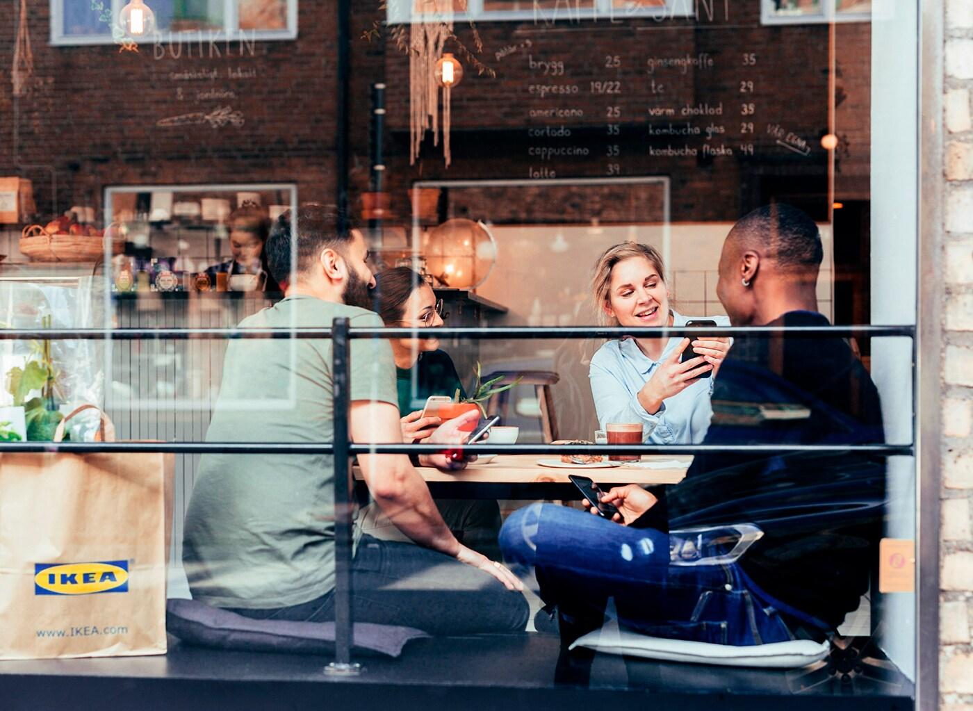 Skupina priateľov sedí na káve v kaviarni s papierovou taškou IKEA vedľa.