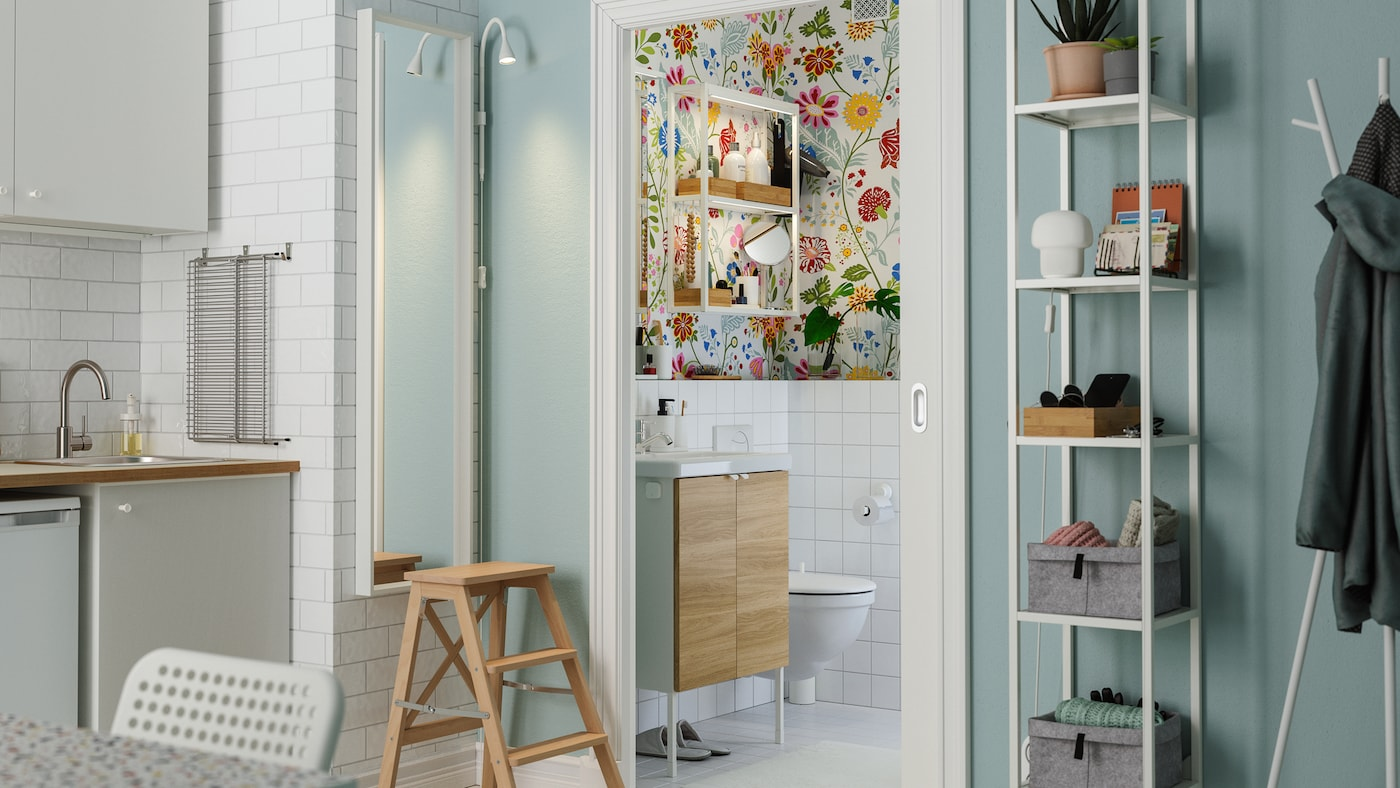 Skydedøre er åbne i et køkken med kig til et farvestrålende badeværelse med blomstret tapet og et lille skab med vask.