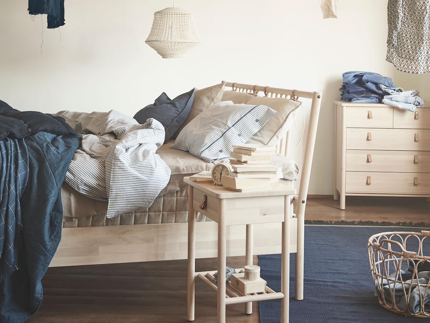 Slaapkamer met BJÖRKSNÄS bedframe, nachttafeltje en ladekast in massief berken, afgewerkt met lichtbruine lederen handgrepen.