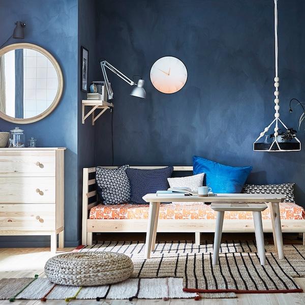 Slaapkamer met blauwe wand en houten meubels