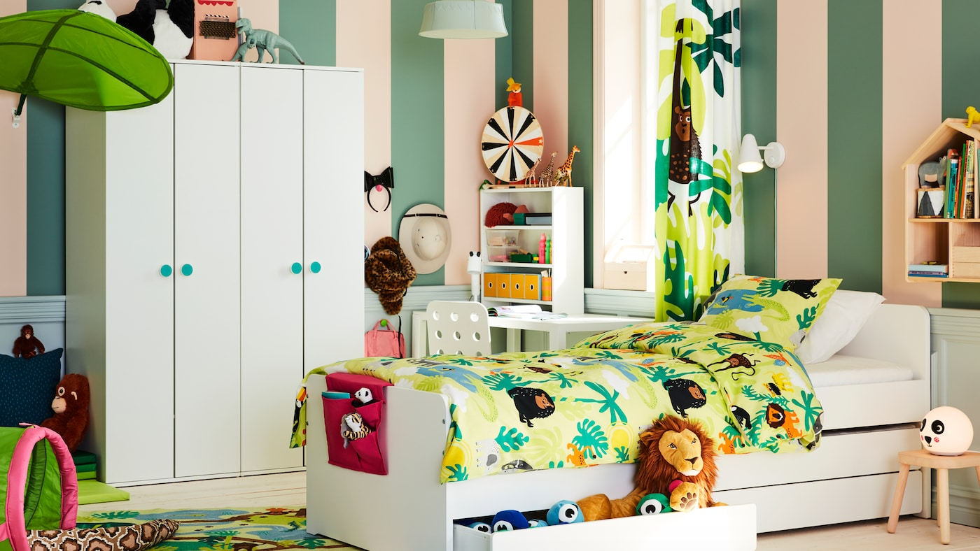 SLÄKT postelja s podposteljnim ležiščem in prostorom za shranjevanje stoji na sredi otroške sobe z motivom džungle, blizu dveh GODISHUS garderobnih omar.