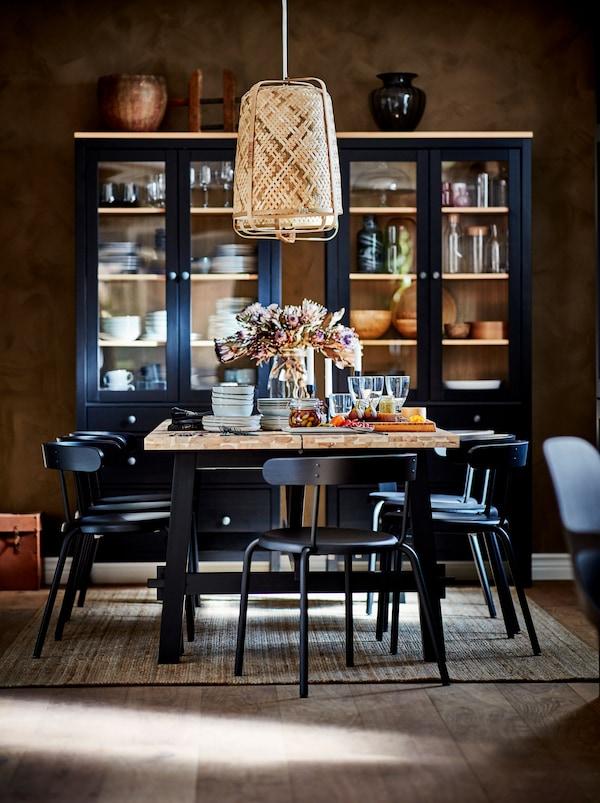 Slávnostne prestretý jedálenský stôl SKOGSTA so závesnou lampou. Pri stene sú vitríny s dvierkami z tmavého skla so stolovacími doplnkami.