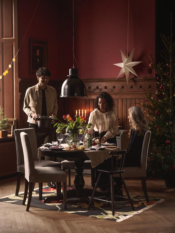 Slávnostne prestretý okrúhly čierny stôl INGATORP. Nad stolom je závesná lampa SVARTNORA za stolom je zavesená hviezda.