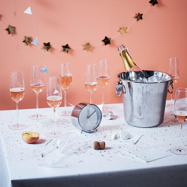 Slavnostně prostřený stůl - bílý ubrus, sklenky s víkem, nádoba na chlazení vína.