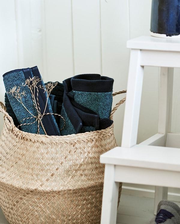 سلة مصنوعة من مواد طبيعية منسوجة، موضوعة بجانب سلّم متدرج أبيض ومليئة بمناشف زرقاء ملفوفة.