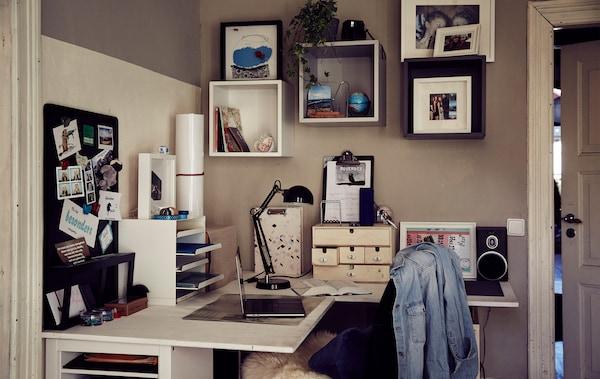 سلة رسائل وصناديق على مكتب زاوية ومن فوقه وحدات تخزين مكعبة على الحائط.