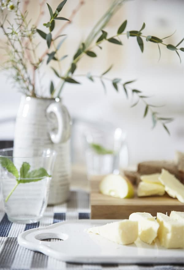 Sliced food on chopping boards, a glass of water and a simple centrepiece in a vase.