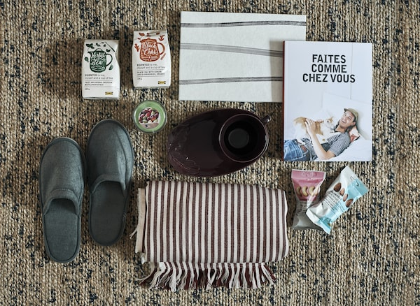 Slippers, books, homewares and snacks arranged on a rug.