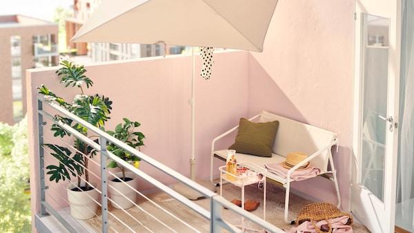 Slnečné popoludnie na mestskom balkóne, kde je v tieni bieleho slnečníka umiestnená biela dvojpohovka INGMARSÖ a svetloružový stolík.