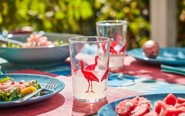 Slnkom zaliaty stôl vonku v letných farbách a vzoroch. Sklenené poháre a ľahké jedlá na tanieroch.