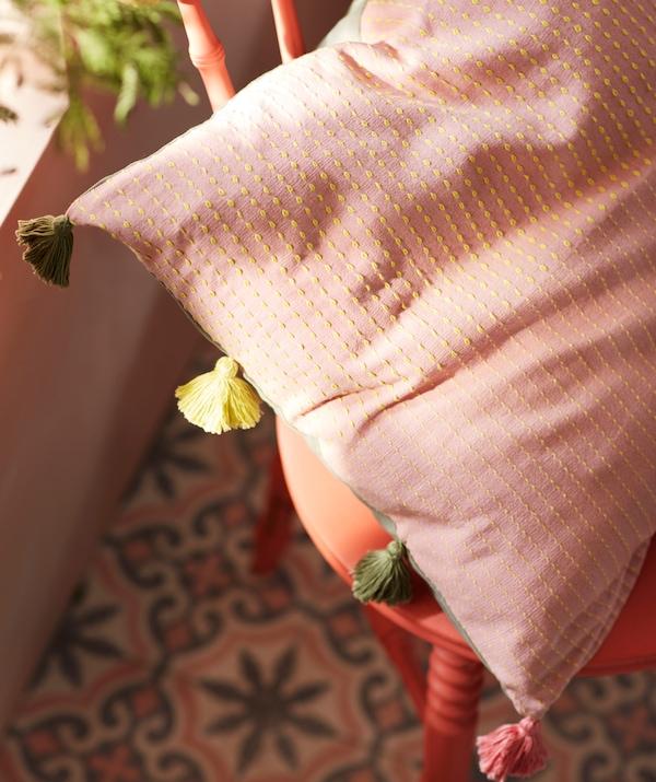 Slnkom zaliaty vankúš na červenej drevenej stoličke. Poťah na vankúš KLARAFINA má vyšívaný vzor a strapce v rôznych farbách.