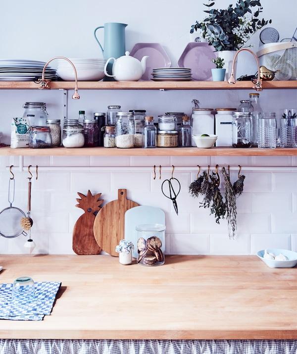 Słoiki do przechowywania i naczynia do serwowania potraw na dwóch drewnianych półkach nad drewnianym blatem kuchennym.