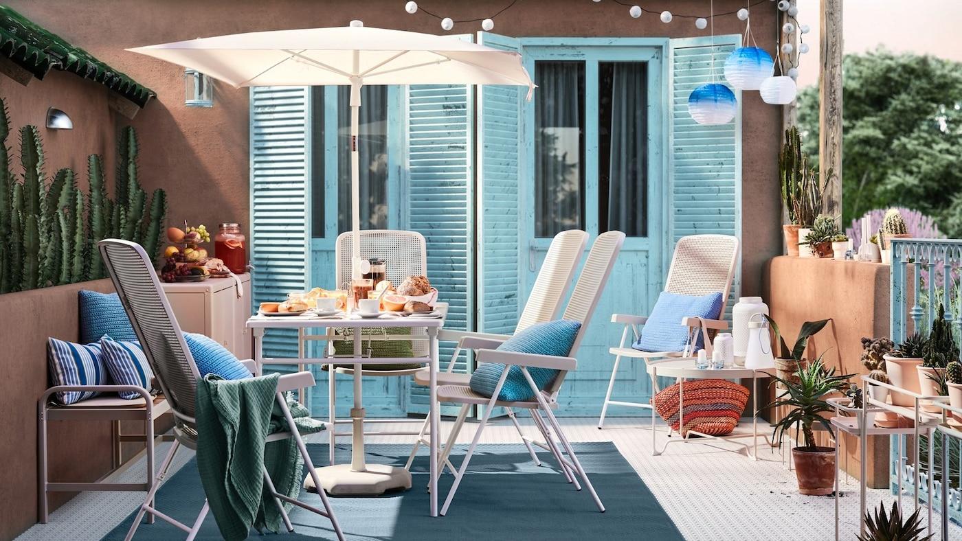 Słoneczne patio ze ścianami wyłożonymi terakotą, niebieskimi drzwiami, białym stołem z parasolem, białymi krzesłami ogrodowymi i niebieskimi poduszkami.