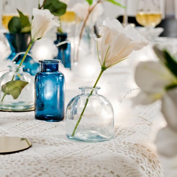 Små blå vaser i olika höjder står på en vit duk med snittblommor i.