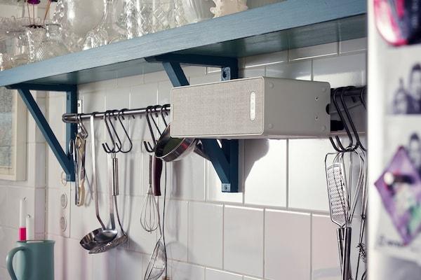 سماعة رف كتب SYMFONISK موضوعة على جدار مطبخ مبلط، بجانب علاقةتتدلى منها أدوات مطبخ.