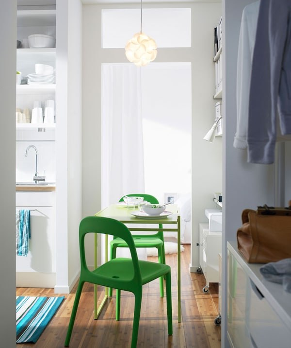 Small apartment with focus on a small green table, setting, and two green chairs facing each other.