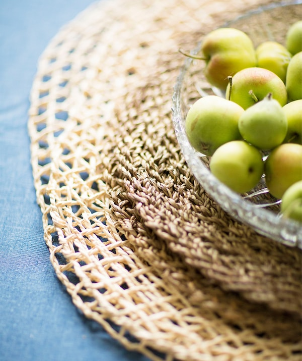 Small apples in a glass bowl on a stack of woven placemats.
