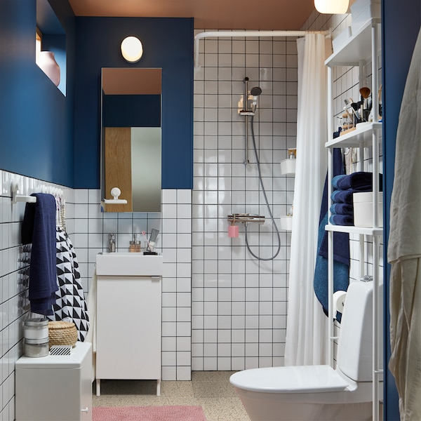 Small bathroom with shower, white furniture, white tiles, dark blue walls, a pink bath mat, a mirror cabinet and blue towels.