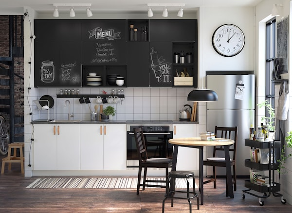Small black and white kitchen with chalk doors inscribed with messages.