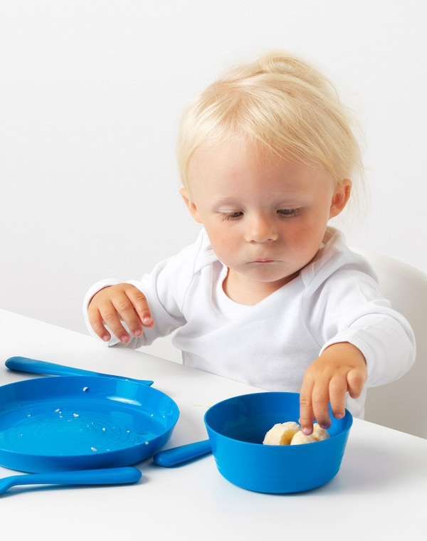 Small boy sitting in a highchair with sliced fruit with blue KALAS tableware.